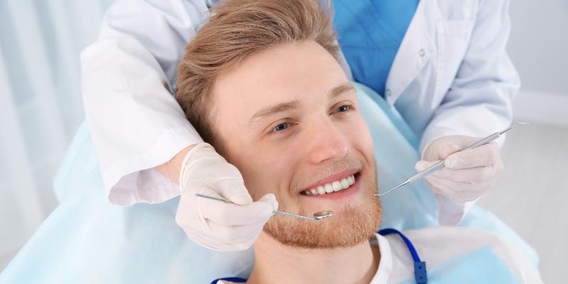 homem sentado na cadeira do dentista sorrindo enquanto esta sendo examinado por aparelhos odontológicos para realizar a raspagem do tártaro