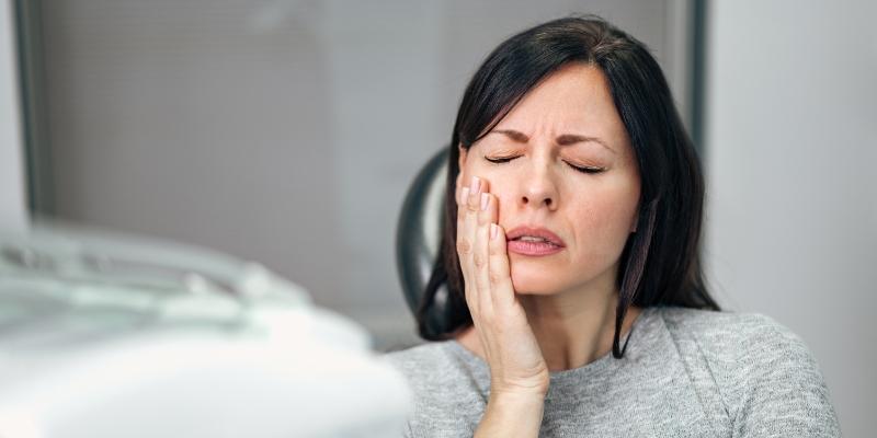 mulher em um consultório odontológico com a mão no rosto  pois está com a gengiva inchada