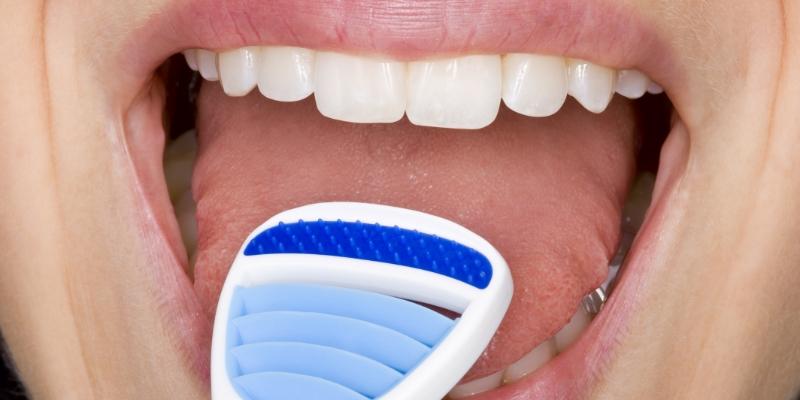 foto de uma boca de uma pessoa que está limpando sua língua com um limpador para tirar mau hálito