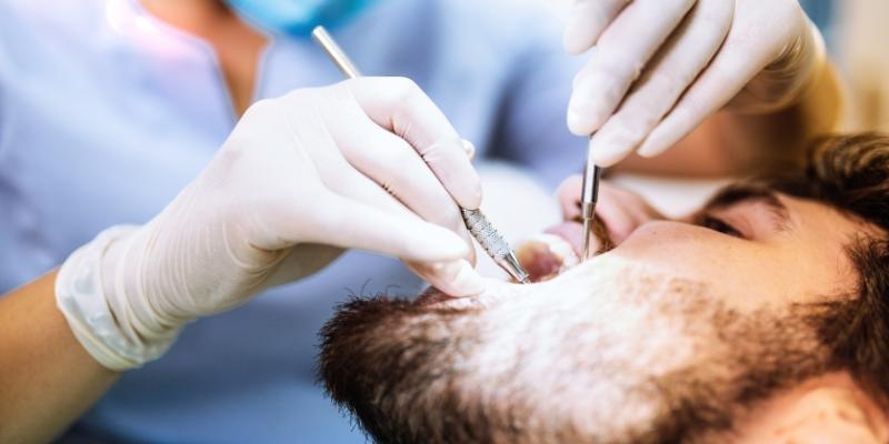 Homem deitado em uma cadeira de dentista realizando tratamentos para cárie e dentista avaliando os dentes com equipamentos odontológicos