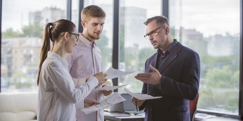 Dois homens e uma mulher analisando como realizar a  redução do turnover