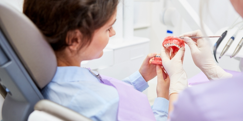 Mulher olhando para uma dentadura para ver como ficará com o aparelho ortodôntico fixo