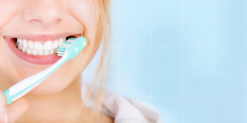 mulher escovando os dentes para evitar  sangramento da gengiva