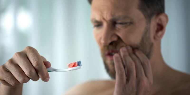 homem com a mão no rosto vendo sua escova suja de sangue pois está com gengivite crônica