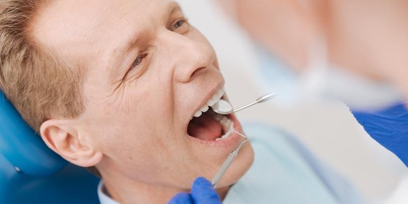 dentista especialista em dtm examinando a boca de seu paciente