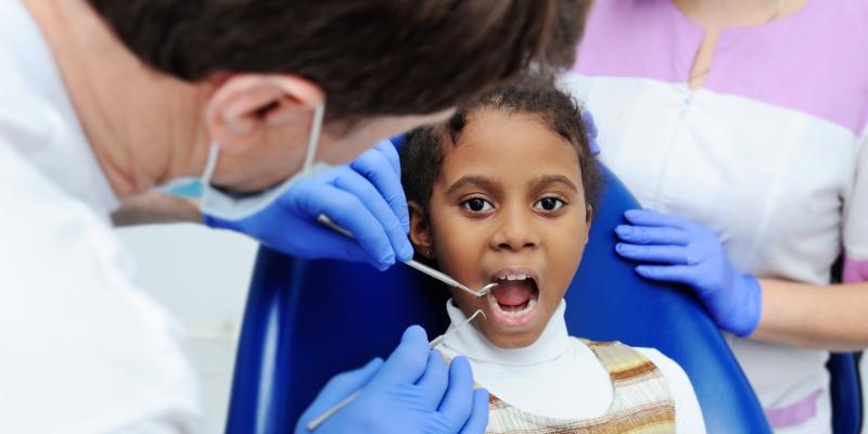 menina em um consultório odontológico sendo examinada por um dentista pois está com cárie em dente de leite