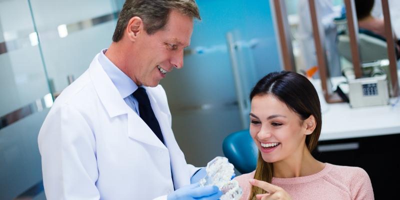 mulher em um consultório odontológico vendo seu dentista explicar como é feita uma cirurgia no dente do siso