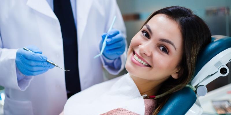 mulher sorrindo em uma cadeira de dentista esperando para realizar uma cirurgia do siso