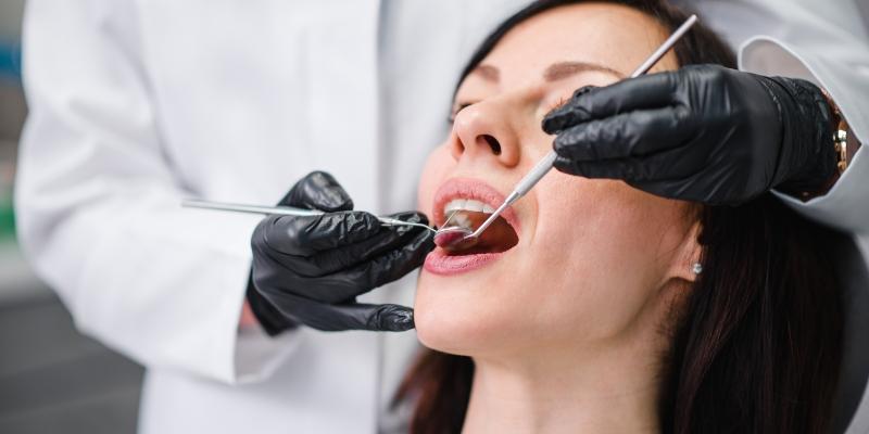 mulher sentada em uma cadeira de dentista sendo examinada por um dentista que está colocando aparelhos na boca para tirar dente do siso