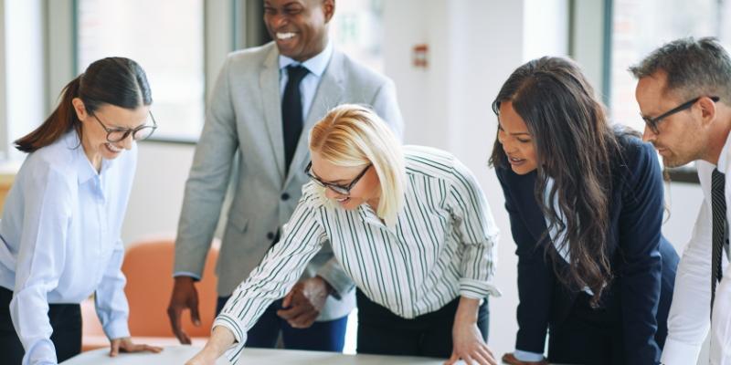 cinco pessoas em volta de uma mesa analisando ações sobre retenção de talentos nas organizações