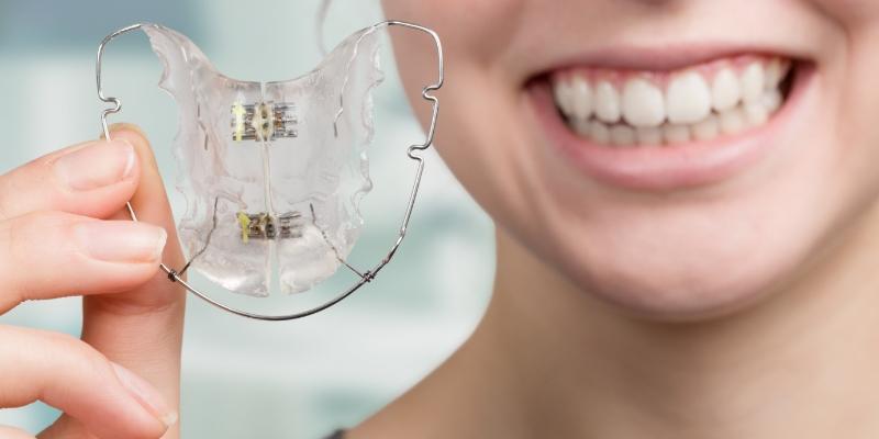 mulher sorrindo segurando um aparelho ortodôntico móvel