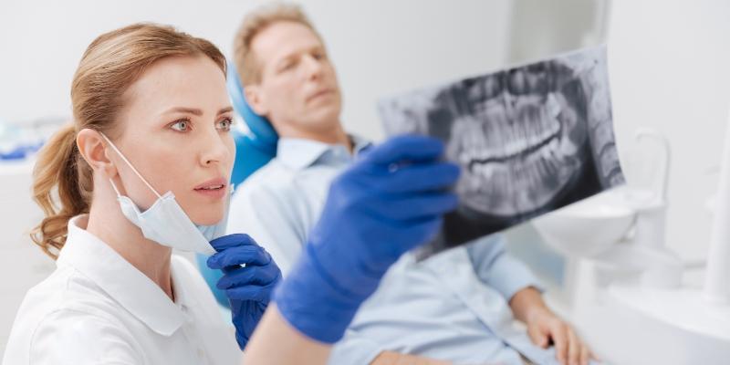 dentista especialista em dtm analisando o exame de seu paciente