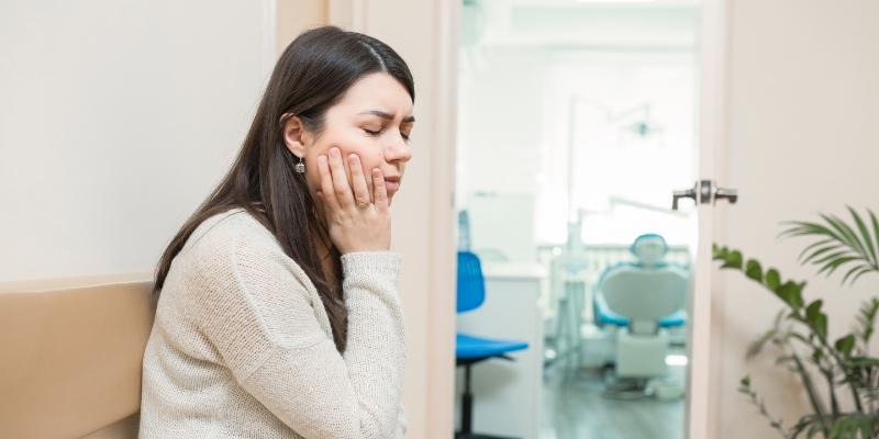 Mulher com a mão na bochecha com feição de dor enquanto espera para realizar um tratamento para dor de dente