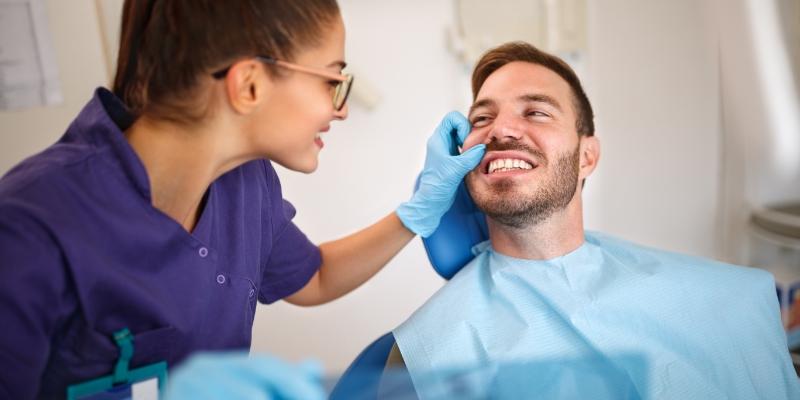 mulher olhando o dente do paciente deitado em uma cadeira de dentista para ver qual o melhor tratamento contra cárie para ser aplicado