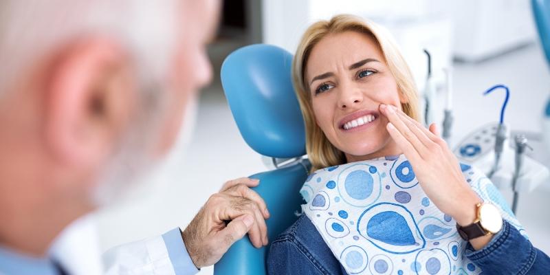 mulher loira deitada em uma cadeira de dentista para realizar restauração de dente colocando a mão no rosto demonstrando dor