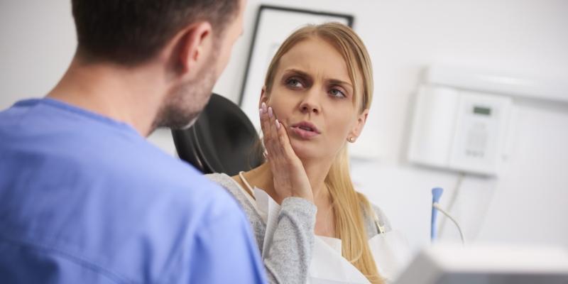 mulher com dor no dente escutando seu dentista explicar as doenças gengivais
