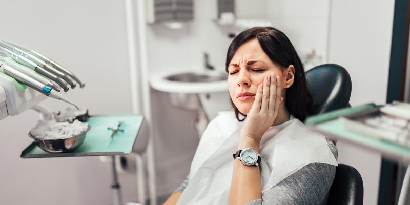 mulher com a mão no rosto pois está com dor no dente e vai ter que tirar dente do siso