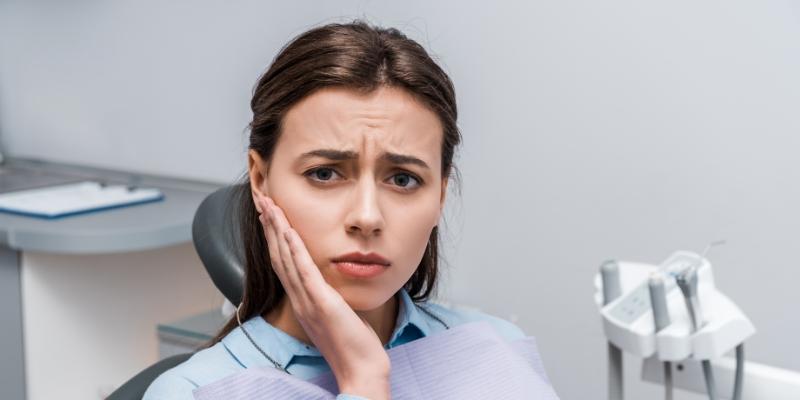 mulher no dentista com a mão no rosto com dor no dente sensível após tratamento de canal