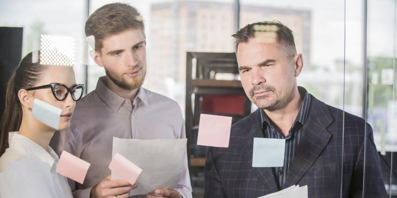 Dois homens e uma mulher parados em frente a um quadro transparente com postites analisando como realizar a  redução do turnover