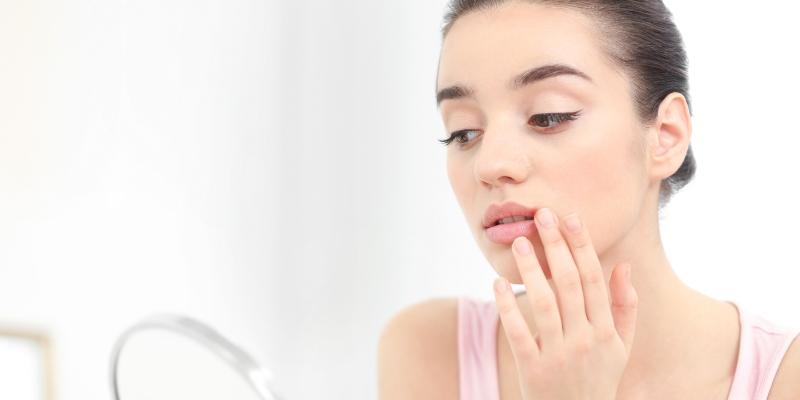 mulher olhando sua afta na boca pelo espelho