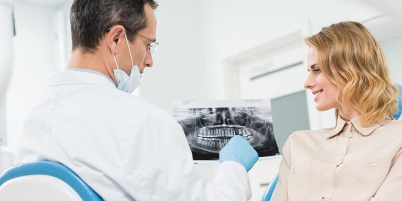 dentista explicando para sua paciente qual é o motivo da sua dor de dente