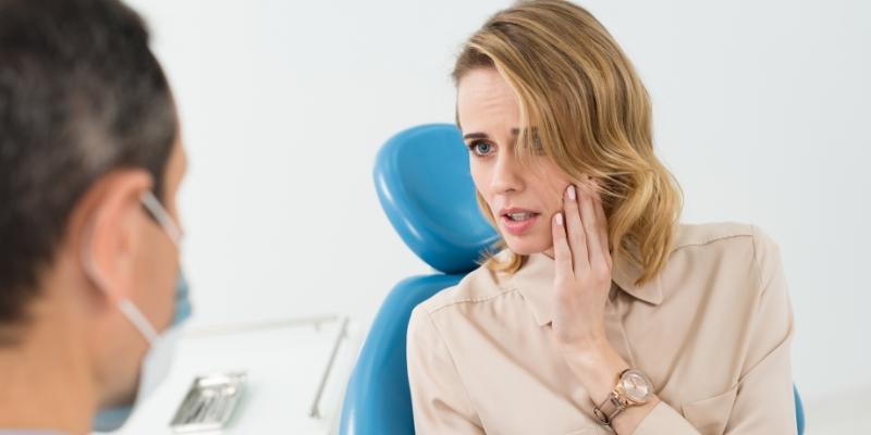 mulher com a mão no rosto em um consultório odontológico pois está com dor na gengiva