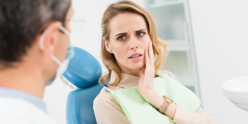 mulher com a mão no rosto em um consultório pois está com dor de dente