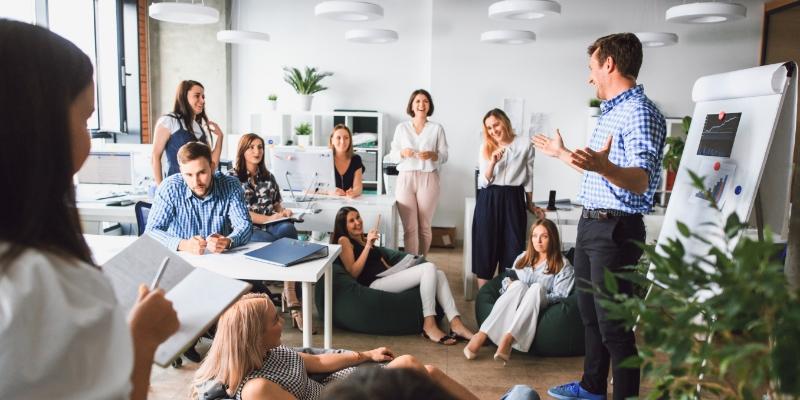 grupo de pessoas em um escritório felizes pois aplicaram  formas de motivar os funcionários