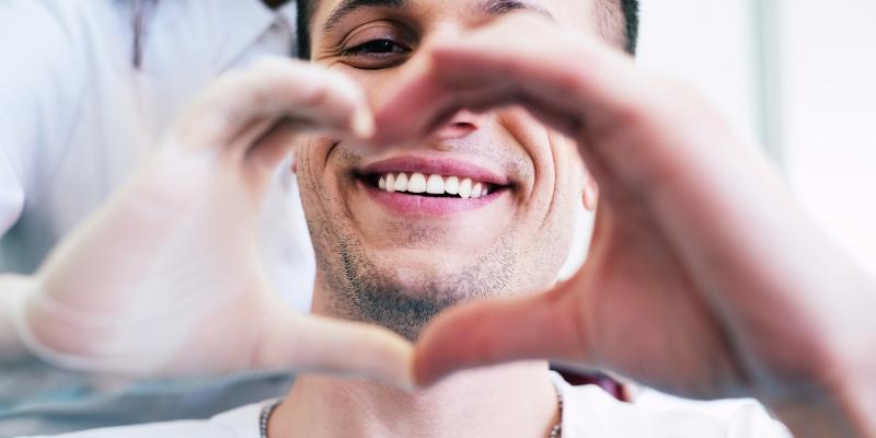 Homem fazendo coração com sua mão e com a mão de sua dentista pois escolheu o melhor plano dentário