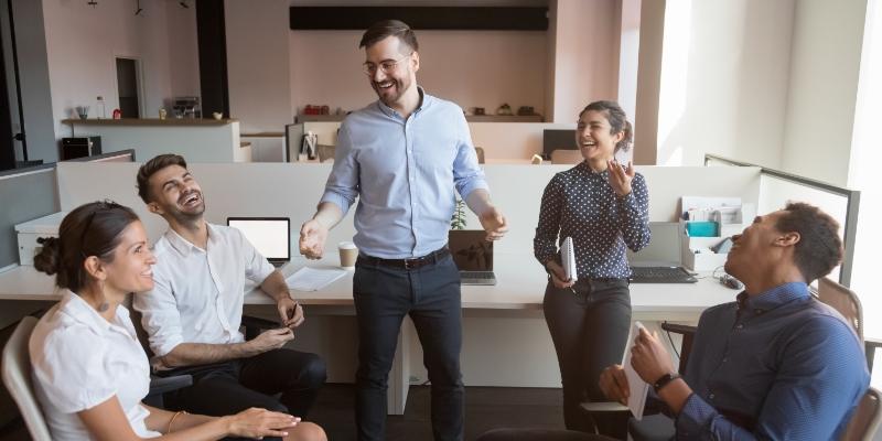 homem falando para outras duas das pessoas da sua equipe ações para melhorar o ambiente de trabalho