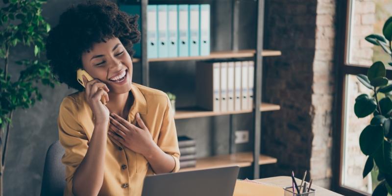 Mulher sorrindo enquanto trabalha pois sua empresa aplica estratégias para aumentar a produtividade