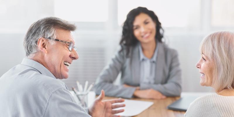 Um senhor e uma senhora indo a um corretor de plano de saúde