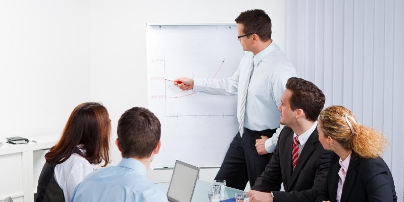homem em uma reunião explicando em um quadro para sua equipe como realizar  ações para motivar funcionários