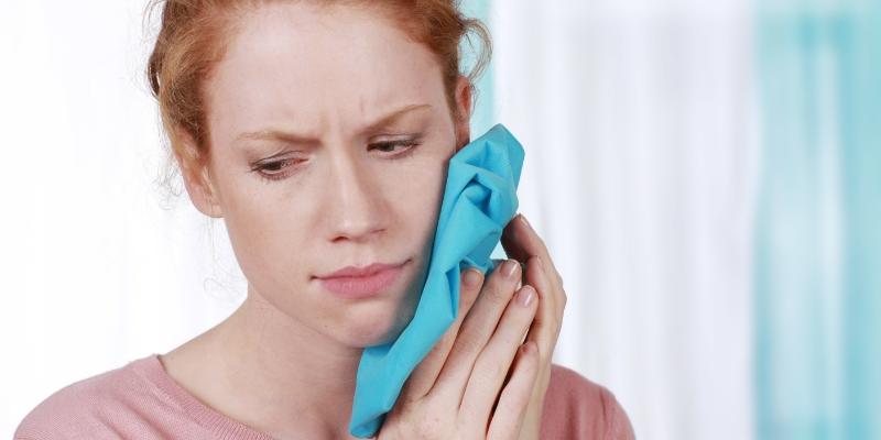 mulher com compressa no rosto pois está com dor no dente siso