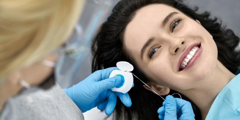 dentista realizando limpeza de dente de sua paciente