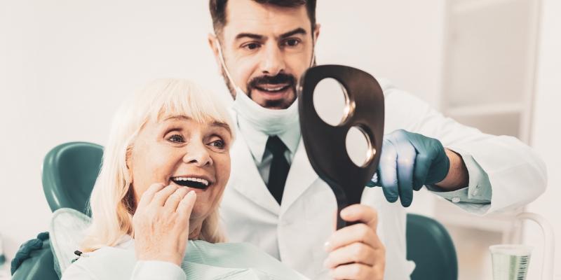 dentista mostrando para uma senhora o resultado de sua dentadura fixa
