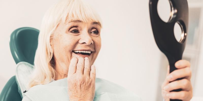 uma senhora vendo o resultado de sua dentadura fixa