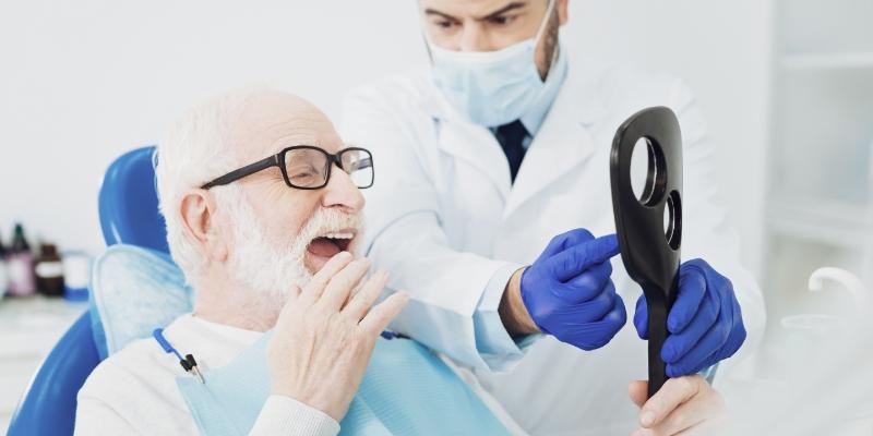 dentista cuidando da  saúde bucal do idoso