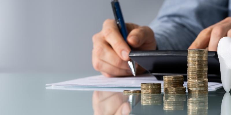 um homem em sua mesa calculando os preços de plano odontológico